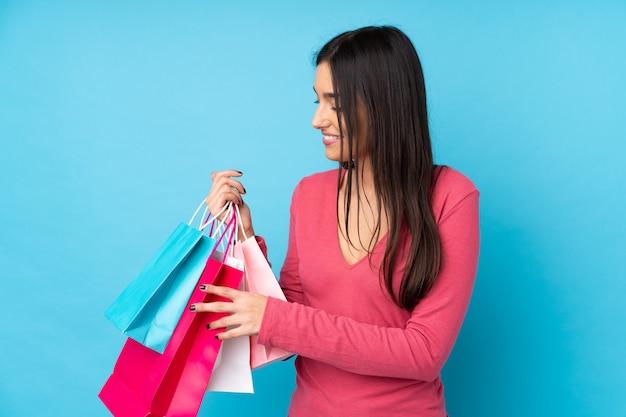 Mujer triguena joven sobre azul que sostiene bolsos de compras