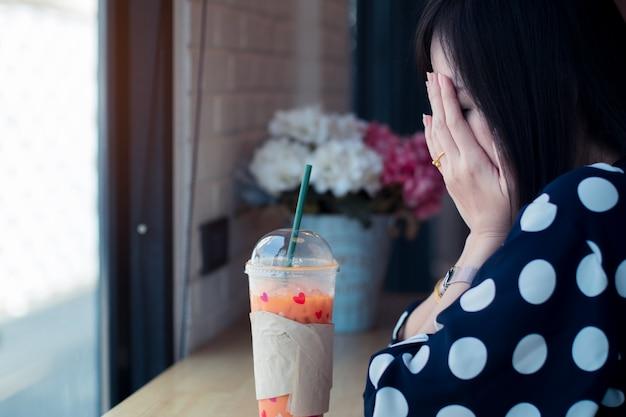 Mujer triste asiática cerca de la ventana pensando en algo con soledad