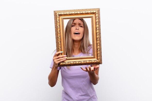 Mujer triste detrás del marco dorado