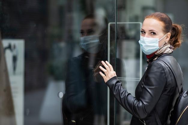 Mujer triste en la entrada de una tienda de ropa cerrada en un centro comercial con una máscara en su rostro. tienda cerrada, tienda por cuarentena, coronavirus, covid-19