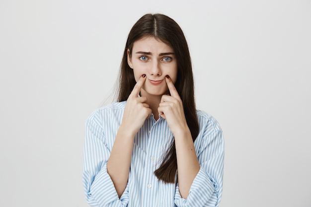 Mujer triste haciendo sonreír con los dedos en la esquina de los labios