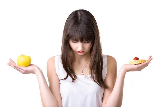 Mujer triste con una manzana en una mano y un pastel en la otra