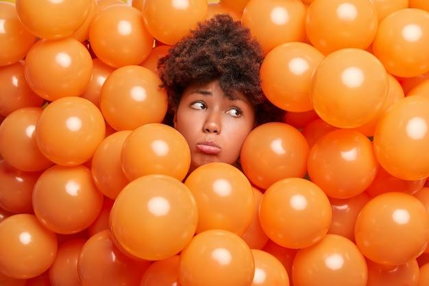 Mujer triste molesta con cabello afro asoma la cabeza a través de globos inflados y mira tristemente lejos, no quiere envejecer rodeada de globos de helio naranja y se siente sola en la celebración de cumpleaños.