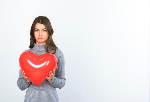Mujer triste de pie con globo de corazón