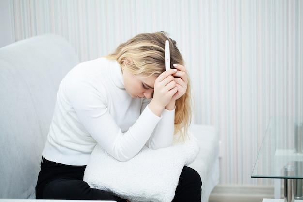 Mujer triste preocupada mirando una prueba de embarazo después del resultado