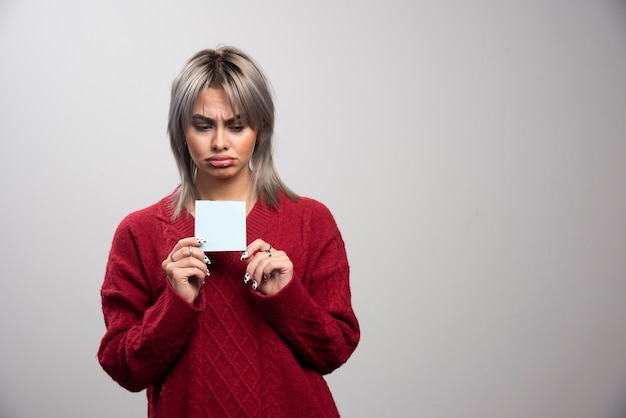 Mujer triste que sostiene el bloc de notas sobre fondo gris. Foto gratis