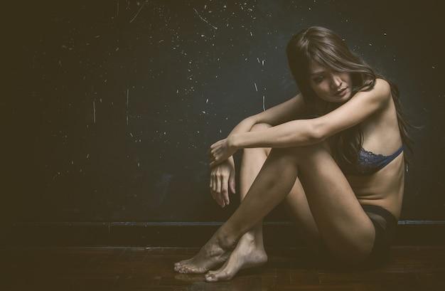 Mujer triste sentada sola en una habitación vacía.