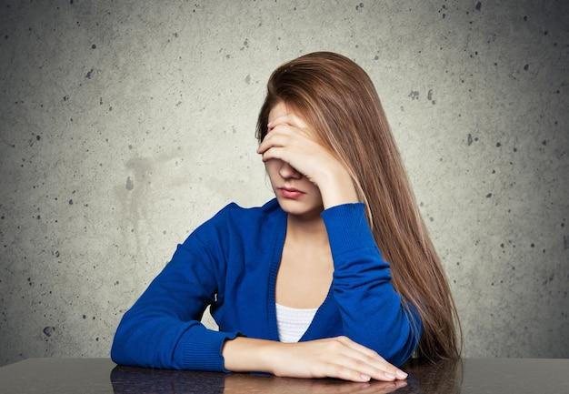 Una mujer triste sentada en el suelo cerca de una pared y sosteniendo su cabeza entre sus manos