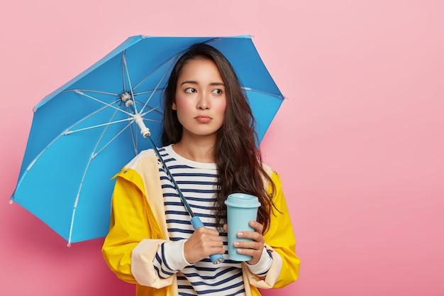 La mujer triste se siente deprimida durante un día lluvioso nublado, tiene depresión estacional, posa bajo un paraguas impermeable, usa un suéter de rayas y un impermeable