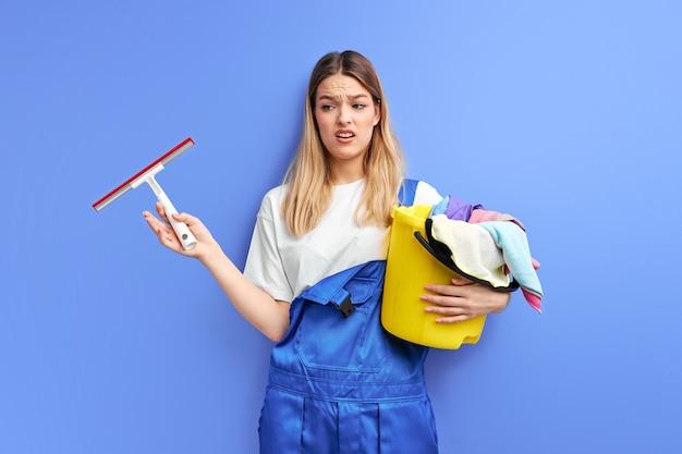 Mujer triste con suministros de limpieza de pie insatisfecho por la suciedad en la habitación que tiene que limpiar, aislado sobre fondo púrpura