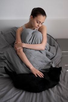 Mujer triste de tiro completo con manta