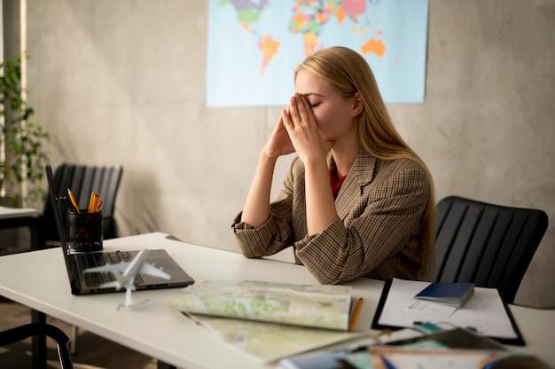 Mujer triste de tiro medio en agencia de viajes