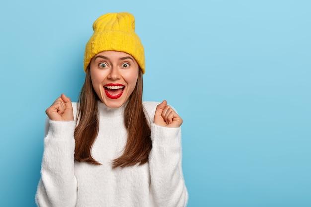 La mujer triunfante aliviada inclina las manos en señal de alegría, aprieta los puños, usa lápiz labial rojo, tiene el cabello lacio oscuro, usa ropa de moda, aislado sobre fondo azul