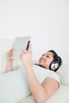 Mujer tumbada en un sofá con auriculares y sosteniendo una tableta táctil