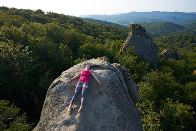 Mujer tumbada relajada encima de la roca de la montaña grande