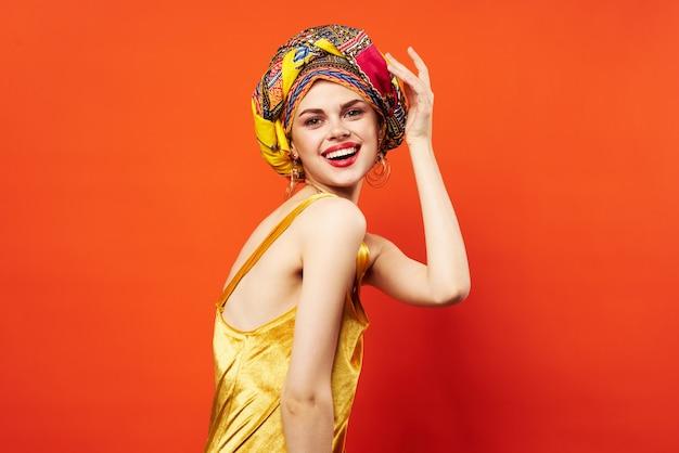 Mujer con turbante multicolor decoración labios rojos encanto pared rojo emociones.