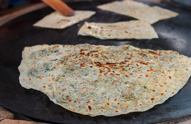 Mujer turca prepara gozleme - plato tradicional en forma de pan plano relleno de verduras y queso