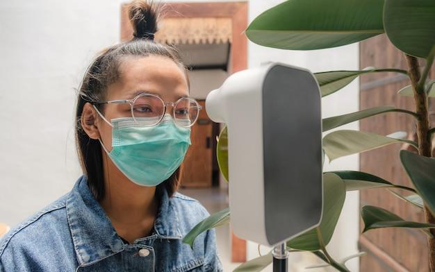 Mujer turista asiática ha comprobado la temperatura corporal con detector de escáner térmico nuevo concepto normal