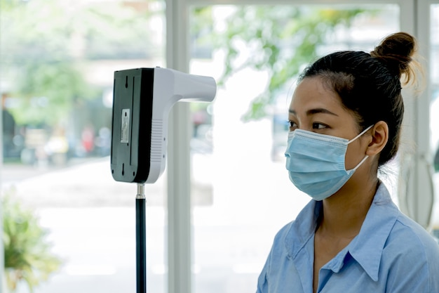 La mujer turista asiática ha comprobado la temperatura corporal con el recorrido del detector de escáner de temperatura térmica.