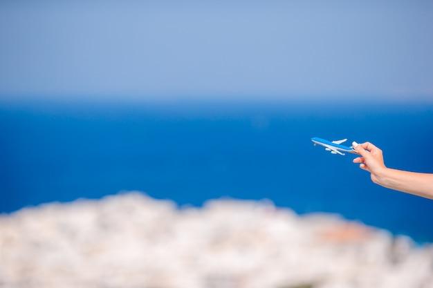 Mujer turista con avión de juguete en manos de fondo del antiguo pueblo griego