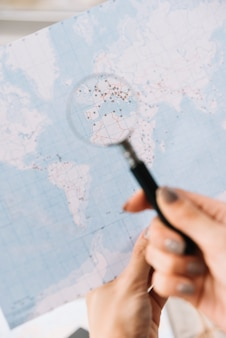 Una mujer turista busca lugares para viajar en el mapa a través de una lupa.