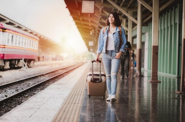 Mujer turista con equipaje en la estación de tren