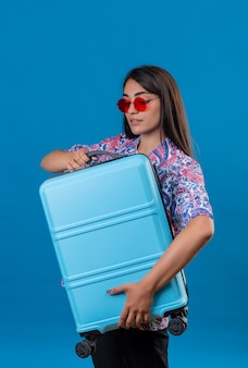 Mujer turista con gafas de sol rojas sosteniendo la maleta de viaje mirando confiado, listo para viajar de pie en azul aislado