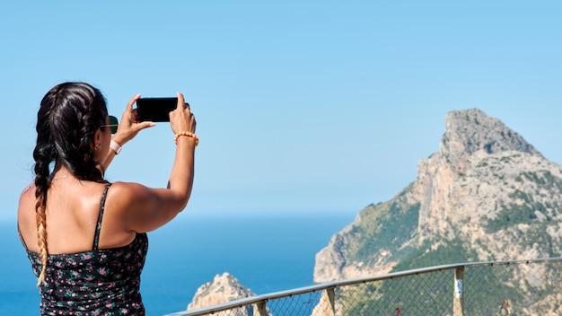 Mujer turista hispana latina tomando fotos desde el smartphone, mallorca, mirador cabo de formentor, paisaje de viajes de europa.