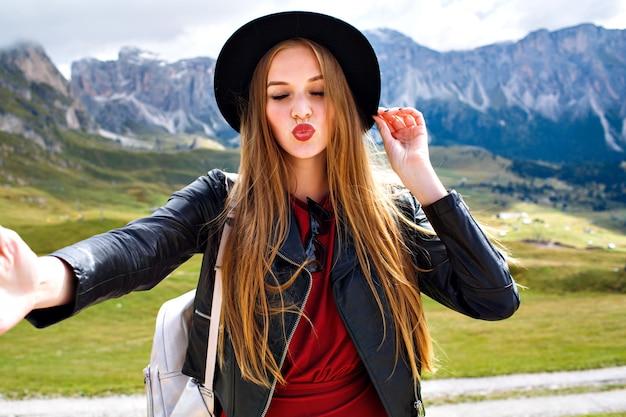 Mujer turista joven bastante alegre con elegante chaqueta de cuero y sombrero de moda, haciendo selfie y cerrando los ojos