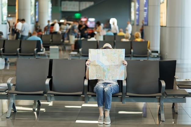 Mujer turista joven viajero cubriendo con mapa de papel, buscando ruta, esperando en el vestíbulo del aeropuerto internacional