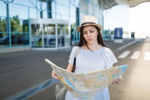 Mujer turista joven viajero insatisfecho con mapa de papel, de pie en el aeropuerto internacional