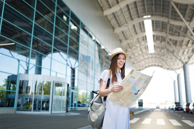Mujer de turista joven viajero sonriente con mochila sosteniendo mapa de papel en el aeropuerto internacional