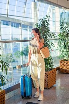 Mujer turista en mascarilla para prevenir virus en aeropuerto internacional.