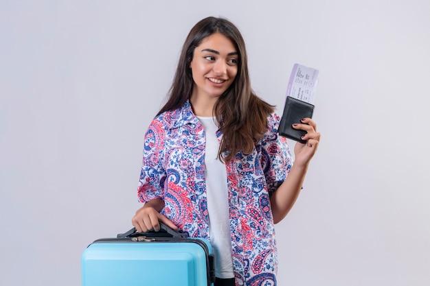 Mujer turista sosteniendo maleta de viaje y pasaporte con boletos mirando a un lado con una sonrisa en la cara feliz y positiva