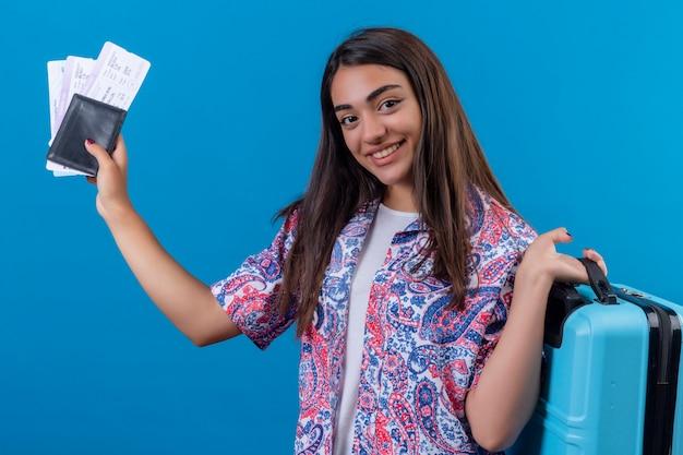 Mujer turista sosteniendo maleta de viaje y pasaporte con boletos con una sonrisa en la cara feliz y positiva