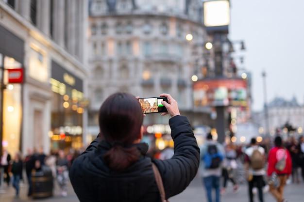 Mujer turista tomando fotos de la ciudad con su celular.