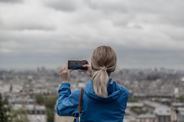 Mujer turista tomando fotos de la ciudad en tiempo nublado