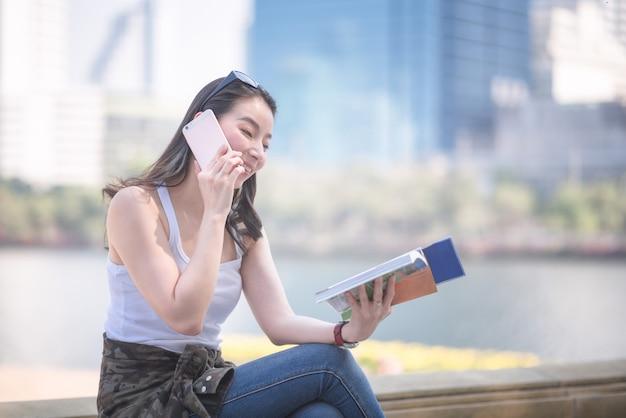 Mujer turística asiática hermosa que lee el libro de guía del viaje que busca para el punto de visita turístico de excursión de los turistas.