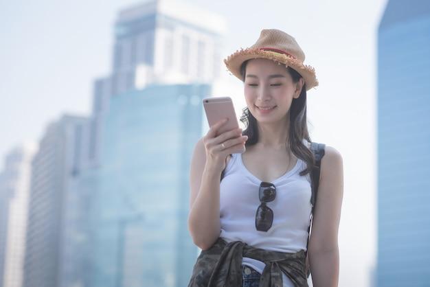 Mujer turística solitaria asiática hermosa que sonríe y que mira el teléfono móvil