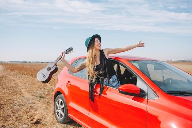 Mujer con ukelele en la ventana del coche