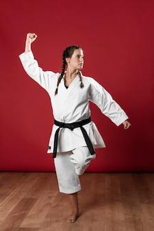 Mujer en uniforme de artes marciales ejercicio de karate