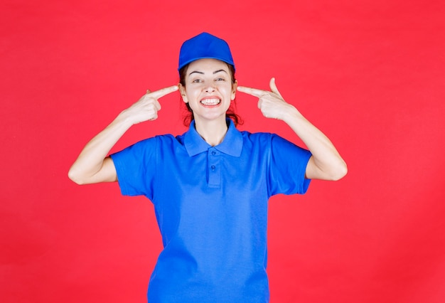 Mujer en uniforme azul apuntando a su sonrisa.
