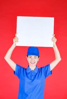 Mujer en uniforme azul y boina sosteniendo un mostrador de información cuadrado blanco y sintiéndose positivo.