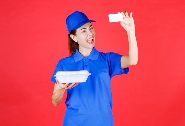 Mujer en uniforme azul sosteniendo una caja de comida para llevar de plástico blanco para la entrega y presentando su tarjeta de visita al cliente.