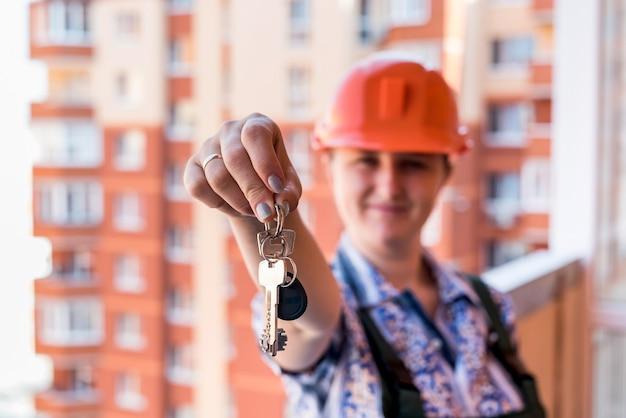Mujer en uniforme y casco mostrando las llaves del nuevo apartamento