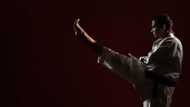 Mujer en uniforme de karate blanco y copia espacio de fondo