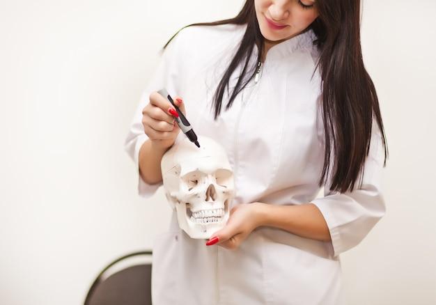 Mujer en uniforme médico sosteniendo una calavera en una mano y muestra con un marcador en varias partes. antropología, educación, ciencia, concepto de anatomía.