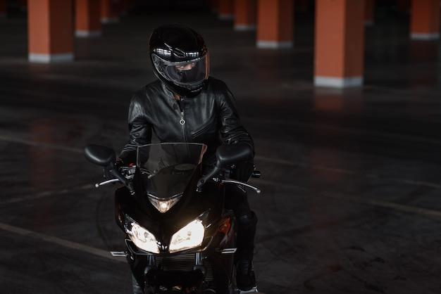 Mujer en uniforme de protección negro, guantes y casco integral montando en su motocicleta en el estacionamiento subterráneo.