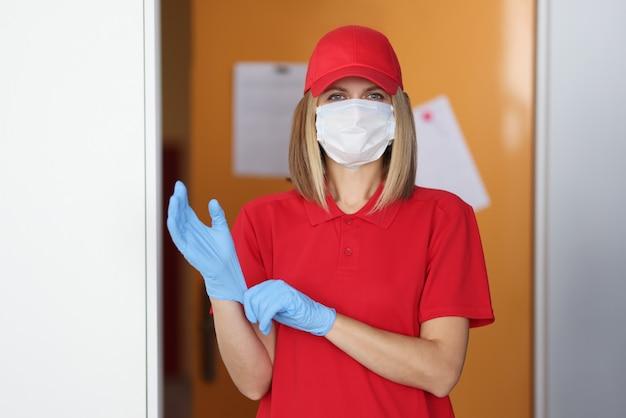 Mujer en uniforme rojo y máscara protectora médica en su rostro pone guante de goma en su mano