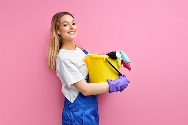 Mujer en uniforme de trabajo azul soporte con balde y trapos posando aislado sobre fondo de color rosa